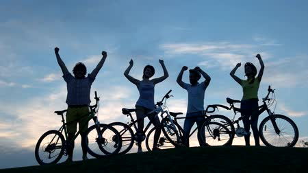bisikletçi : Young dancing cyclists at sunset sky. Group of young cheerful friends having rest outdoors. Happy people dancing at sunset.