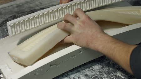 gips : Close up molding a gypsum cornice. Mans hands holding silicone mold for producing cornice. Production of luxury frames.