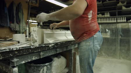 gips : Worker made a part of gypsum cornice. Specialist separating ready part of cornice from gypsum at manufacture. Molding a cornice at manufactory.