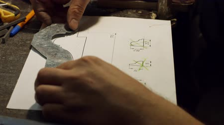 compares : Expert compares the sizes of sketch. Craftman applying a metal ruler to the drawing. Working with a new project. Creating a construction detail. Mechanical engineering concept. Stock Footage