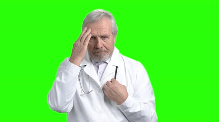 nyomasztó : Nervous sad doctor portrait. Senior old physician sad about patient death. Green screen hromakey background for keying.