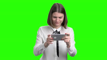 temper : Excited girl playing video games on smartphone.Green screen hromakey background for keying.