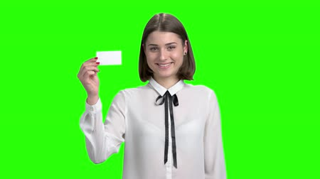 product promo : Cute young girl shows blank business card. Portrait of brunette smiling girl. Green screen hromakey background for keying.
