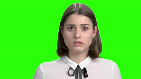 обеспокоенный : Young worried girl hearing bad news. Facial expressions, upset, thrilled and nervous. Green screen hromakey background for keying.
