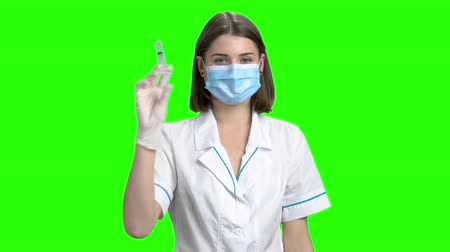 иммунизация : Portrait of young female doctor prepare syringe. Physician in white medical uniform. Green screen hromakey background for keying.