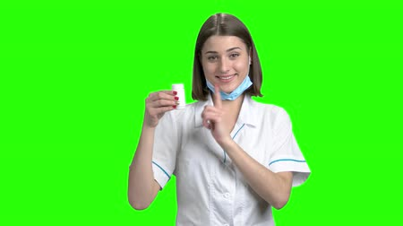 продвигать : White can of pills promotion, thumb up. Young brunette smiling female doctor recommed pills. Green screen hromakey background for keying. Стоковые видеозаписи