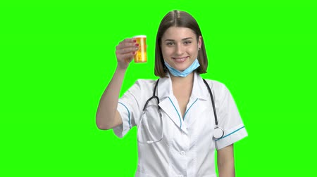 продвигать : Young female doctor advertising yellow can of pills. Green screen hromakey background for keying.
