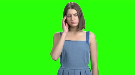 хмурый : Young woman having headache. Touching head. Green screen hromakey background for keying. Стоковые видеозаписи