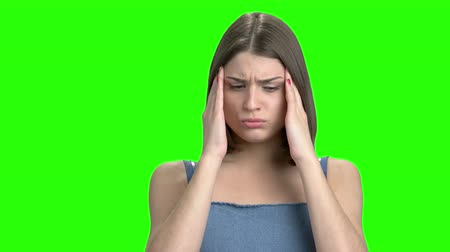 хмурый : Portrait of stressed woman having pain in her head. Green screen hromakey background for keying.
