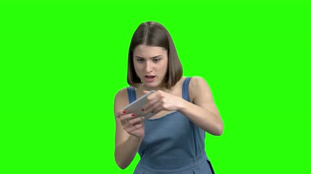 keying : Teen girl gamer playing video game on smartphone. Small portable device, enthusiastic play. Green screen hromakey background for keying.