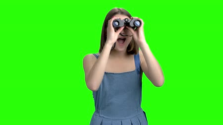 binocular : Teen girl use binoculars, front view. Portrait of woman in denim dress looks throug binocular. Green screen hromakey background for keying. Stock Footage