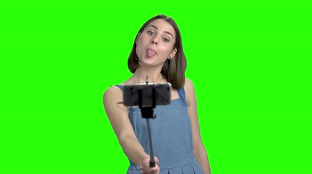 fool : Girl making selfie with selfie stick. Green screen hromakey background for keying.