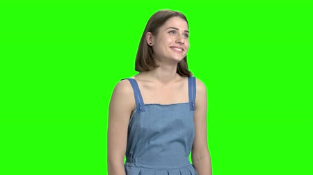 crush : Cheerful smiling woman in denim dress flirting on camera. Front view, cute brunette girl. Green screen hromakey background for keying. Stock Footage