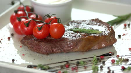 kakukkfű : Steak close up. Meat, cherry tomatoes and sauce.