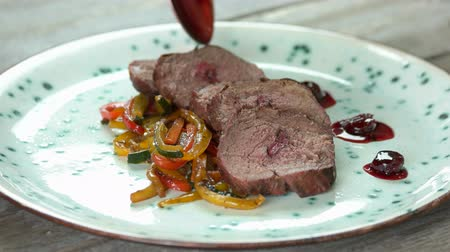 veal recipe : Spoon pouring sauce on dish. Veal tenderloin with vegetables.