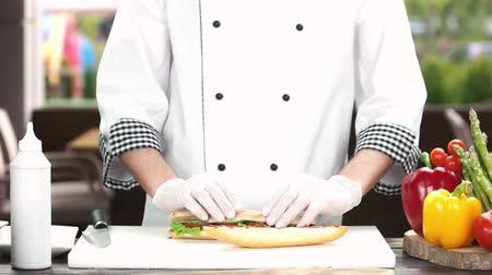 калория : Hands of chef preparing sandwich. Bun, vegetables and sausage. Стоковые видеозаписи
