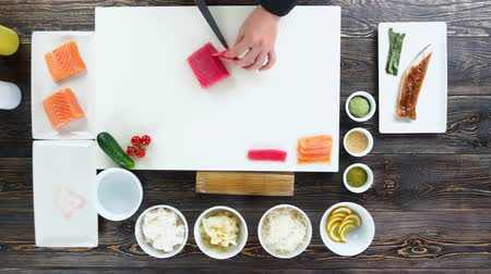 california rolls : Sushi preparation, wooden table. Hands cutting tuna. Stock Footage