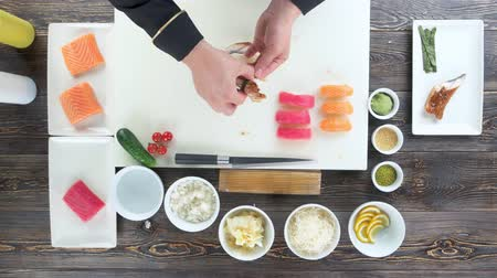 нигири : Hands of chef preparing sushi. Rice, smoked eel and seaweed.