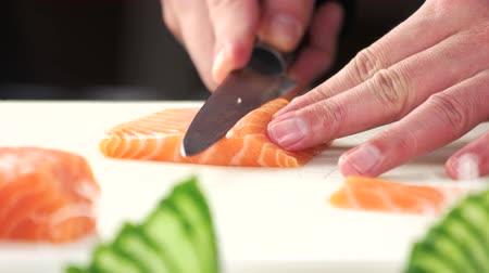 cutting up : Chef slicing salmon close up. Raw fish on cutting board.