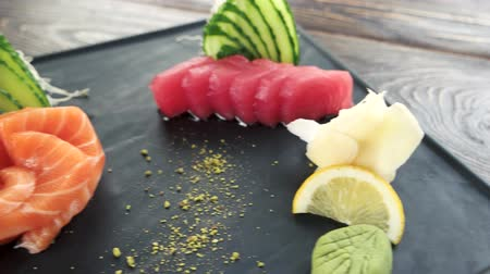 pistacje : Sashimi plate on the table. Raw fish, ginger and cucumber.