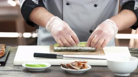 унаги : Chef making unagi sushi. Rice, avocado and smoked eel.