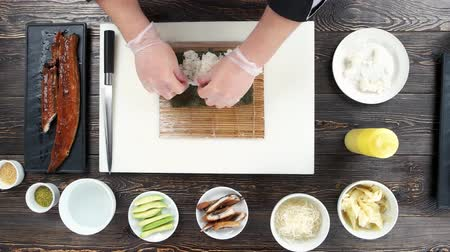 chefs table : Sushi preparation, rice and nori. Hands making food top view.
