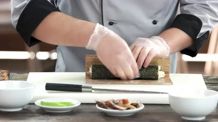 seafood dishes : Chef shaping a sushi roll. Japanese food preparation, bamboo mat. Stock Footage