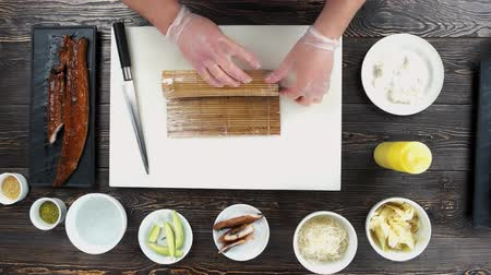 унаги : Chef making sushi, bamboo mat. Hands preparing food, wooden table.