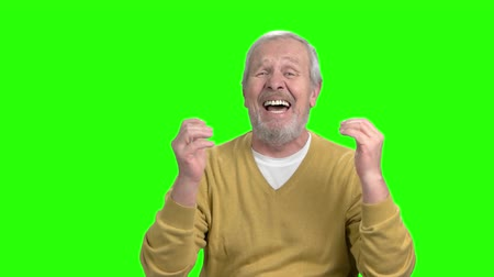 regret : Desperate elderly man gesturing with hands. Stressed and troubled old man screaming on chroma key background, slow motion. Human facial expressions.