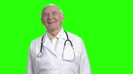 splatnost : Front view laughing doctor. Old doctor with stethoscope is laughing, green hromakey background.