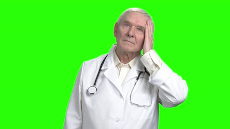 splatnost : Serious grave earnest doctor. Portrait of frowning old doctor touching his face, green hromakey background for keying.