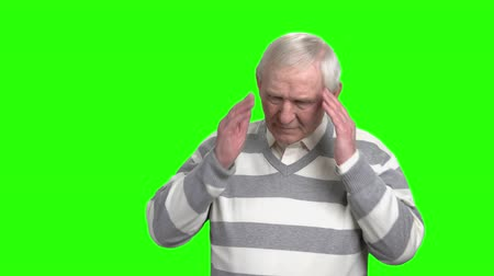 pena : Old man has a headache. Grandpa regretting about something. Green hromakey background.