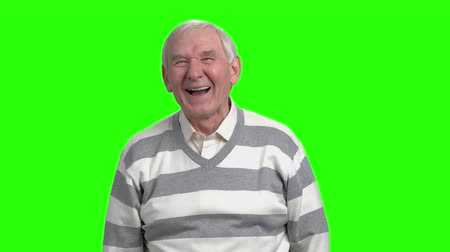energized : Old man laughing in green studio, slow-motion. Friendly grandfather laughing against green hromakey background.