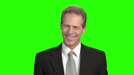 energized : Portrait of cheerful mature businessman. Man in suit facial expressions, mouth motion. Green hromakey background for keying. Stock Footage