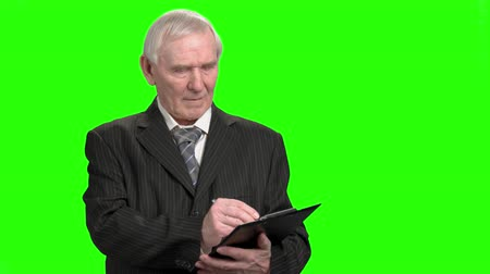 inspector : Portrait of senior businessman writing down on clipboard. Old man in suit attentively writing down on clipboard, green hroma background.