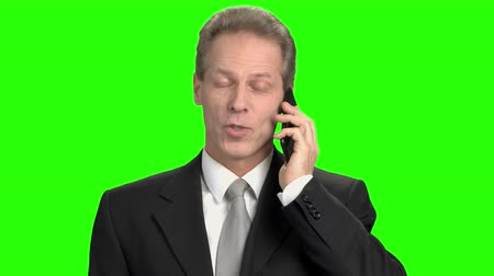 publicity : Pleasant cheerful business man talking on phone. Portrait of cheerful mature man with phone in green hromakey background. Stock Footage