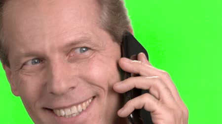 publicity : Close up smiling mature man face talking on phone. Male mature face talking on smartphone, macro close up view, green hroma screen background. Stock Footage