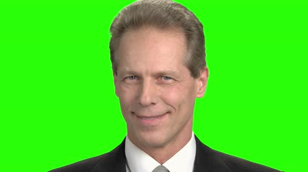 urge : Facial emotions, cheers and suspect. Close up mature man smiling with teeth, green screen hromakey background.