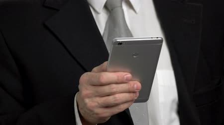 připomínka : Close-up back view smartphone typing. Smartphone typing by one hand, businessman in suit. Phone back side.