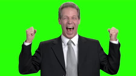 energized : Extremely happy businessman in suit. Business man loudly laughing with teeth and rejoicing, green hroma background.