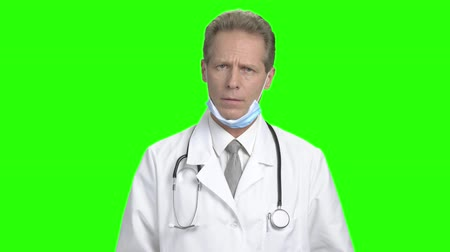 bandaj : Worried male doctor on green background. Serious and troubled mature doctor on chroma key background. Stok Video
