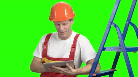 substituição : Positive builder with digital tablet. Male caucasian architect working with a computer tablet standing on green background. Smiling construction worker with modern pc tablet.
