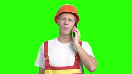 alpha cell : Serious foreman talking on cell phone. Mature engineer in yellow helmet talking on mobile phone standing on green screen background.