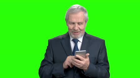 вырезка : Smiling businessman typing a message on smartphone. Happy elderly businessman with modern mobile gadget, Alpha Channel background.