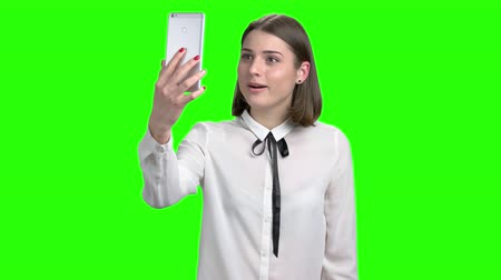köszönt : Teen girl in white blouse talking through web cam of her smartphone. Happy, cheerful and smiling woman. Green screen hromakey background for keying.