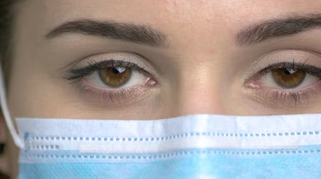 носить : Extreme close up brown eyes with medical mask. Brown-eyed female doctor eyes.