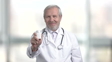 efektivní : Aged doctor holding bottle with pills. Senior male doctor with pills showing thumb up. New effective medical product.