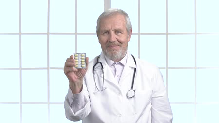 antibiotici : Elderly doctor smiling with blister of pills. Happy senior doctor showing pills and gesturing thumb up. Cheerful doctor on window background. Filmati Stock