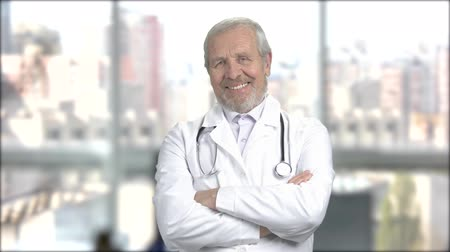 stojan : Joyful mature doctor, portrait. Happy senior doctor folded arms standing on window city background. People, professions, emotions.