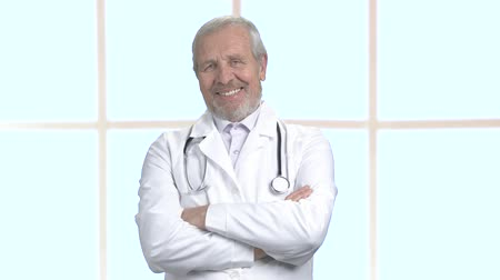 hanedan arması : Cheerful male doctor with arms crossed. Smiling senior doctor on clinic window background, portrait. Face of happy doctor.